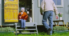 4K Cheerful senior couple relaxing outside gypsy caravan on a bright autumn day. Stock Footage
