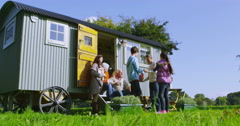 4K 3 Generations of a happy family relaxing outside gypsy caravan in autumn Stock Footage