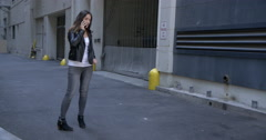Young woman in leather jacket stands and uses cellphone in alley 4K Stock Footage