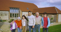 4K Portrait happy family of 3 generations standing outside countryside home Stock Footage