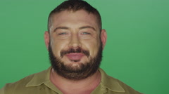 Muscular man attempts to make silly faces, on a green screen  background Stock Footage