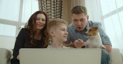 Happy family with a dog the Jack Russell Terrier talking to relatives via video Stock Footage
