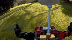Racing drone quad copter flying FPV through trees in park on sunny day Stock Footage