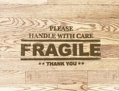 Fragile word stamp on wood plank background Stock Illustration