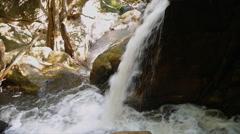Waterfall flowing through big rock Stock Footage