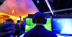 Gamer against computer tv monitor screen playing video games at E3 2016 expo Stock Footage
