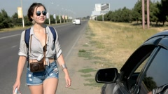 Traveler woman hitchhiking on a sunny road Stock Footage