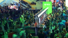 Pan across crowds gamers playing games Microsoft XBOX booth E3 2016 expo Stock Footage