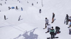Ski resort. Snowboarder ride on slope, jump om springboards. Mountain. Sunny day Stock Footage