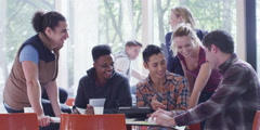 Cheerful diverse student group chatting & working together in college cafe area Stock Footage