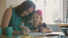 Beautiful young mother is helping her blond little daughter to colour a picture Stock Footage