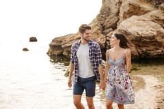 Young couple in love walking at the beach holding hands Stock Photos