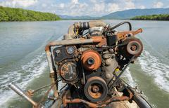 The engine of a long-tail boat with boat wake Stock Photos