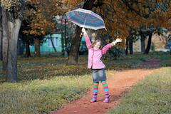 Happy little girl with umbrella in park autumn season Stock Photos