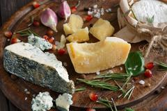 Cheese delikatessen closeup on rustic wood, blue roquefort and parmesan Stock Photos