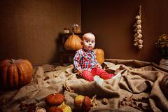 Cute baby in checked shirt and red pants sitting in room with seasonal Stock Photos