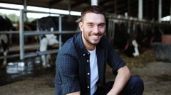 Man or farmer with cows in cowshed on dairy farm Stock Footage