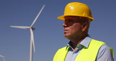 Close View Technical Engineer Foreground Supervising Wind Turbines installation Stock Footage