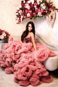 The beautiful brunette woman with tender makeup posing in a pink wedding dress Stock Photos