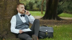 Man in a green park talking on the phone Stock Footage