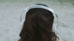 Camera goes from a female head in the headphones through the sea Stock Footage