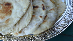 Indian woman hands serve Naan flatbread Stock Footage