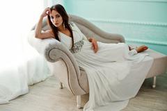 Sensual woman in white dress on sofa Stock Photos