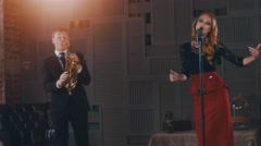 Jazz duet perform on stage. Saxophonist in suit. Vocalist in retro style Stock Footage