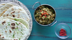 Indian woman hands serve Alu Methi with Naan flatbread Stock Footage