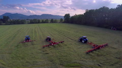 Three tractors are turning the hay around on a beautiful meadow Stock Footage