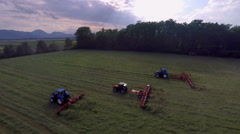 Three tractors with rotary rakes working in the meadow Stock Footage