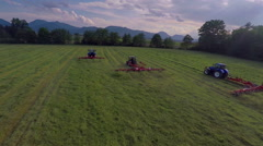 Three tractors are working in a big green meadow Stock Footage