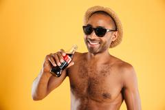 Cheerful young man in hat and sunglasses drinking coke Stock Photos