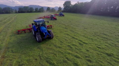 Three tractors are working in three separate lanes on a big meadow Stock Footage