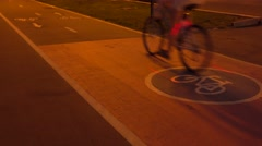One bicycle passing by on urban bike path at night. 4K clip Stock Footage