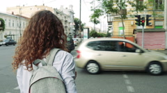 Slender woman with curly hair and a backpack waiting for the green traffic light Stock Footage