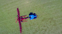Slowly moving across the field with a big blue tractor to turn hay around Stock Footage