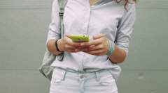 Close-up of slim woman in jeans and shirt uses green mobile phone Stock Footage