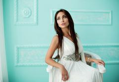 Sensual woman in white dress on arm-chair Stock Photos