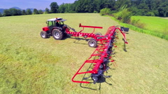 Lowering rotary rakes to the ground and starting to move hay around Stock Footage