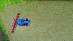 Blue tractor has stopped but the rotary rakes are still moving on a big lawn Stock Footage