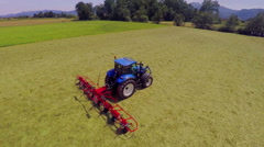 Blue tractor has started rotary rakes and the work has begun Stock Footage