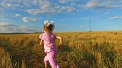 Girl child running across the field. Stock Footage