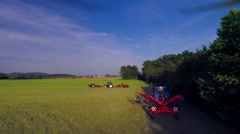 Three tractors are busy raking hay on a hot summer day Stock Footage