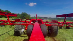 Big tractor is pulling a huge machine with rotary rakes behind it Stock Footage