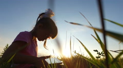 Little girl with enthusiasm plays on the tablet PC. Stock Footage