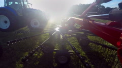 Rotary rakes start moving and a farmer will begin working on the meadow Stock Footage