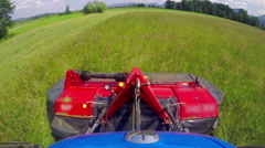 A huge blue tractor is driving on the field of grass Stock Footage