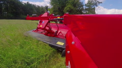 Cutting grass with a big red grass cutting machine Stock Footage