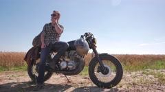 Stylish man smoking on the vintage custom cafe racer in a field Stock Footage